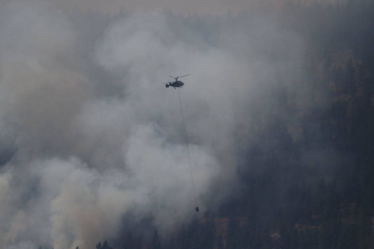 A BCWS helicopter flies against the black smoke of a new wildfire on Westside Road in the Central Okanagan. (Aaron Hemens photo)