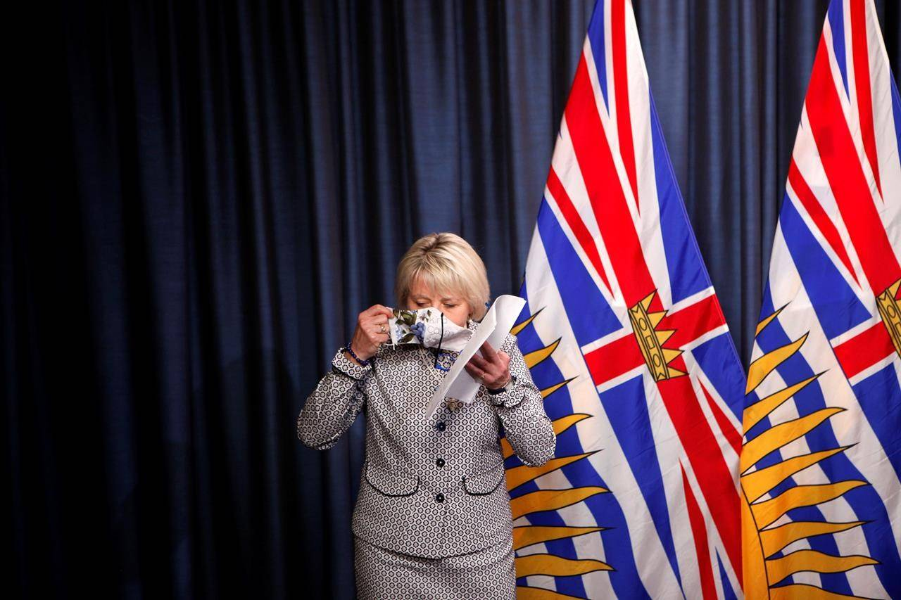 Provincial health officer, Dr. Bonnie Henry, puts on her protective mask after releasing details about a COVID-19 vaccination card that will be needed by anyone wanting to eat in restaurants, visit theatres or go to other events. She made the announcement at a news conference at the B.C. legislature in Victoria on Monday, Aug. 23, 2021. THE CANADIAN PRESS/Chad Hipolito