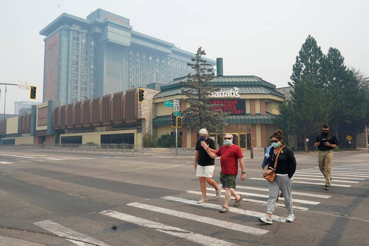 Harrah's Lake Tahoe Casino is shrouded in smoke as face mask wearing pedestrians cross the street at the California-Nevada line, Tuesday, Aug. 24, 2021. Smoke from the Caldor Fire is blanketing the area cloaking the normally blue sky in a dull gray aura. (AP Photo/Rich Pedroncelli)