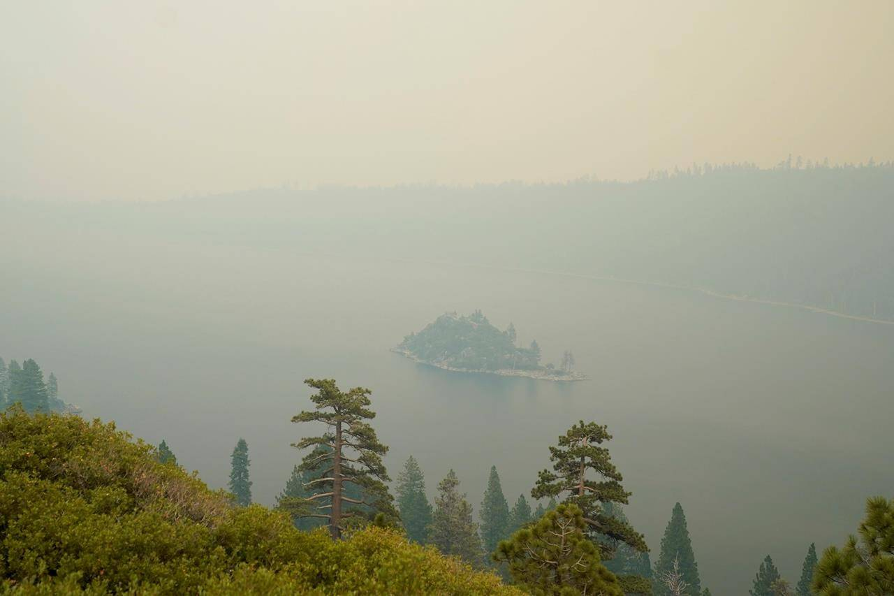 Lake Tahoe's Emerald Bay is shrouded in smoke from the Caldor Fire, near South Lake Tahoe, Calif., Tuesday, Aug. 24, 2021. The massive wildfire, that is over a week old, has scorched more than 190 square miles, (492 square kilometers) and destroyed hundreds of homes since Aug. 14. It is now less than 20 miles from Lake Tahoe. (AP Photo/Rich Pedroncelli)