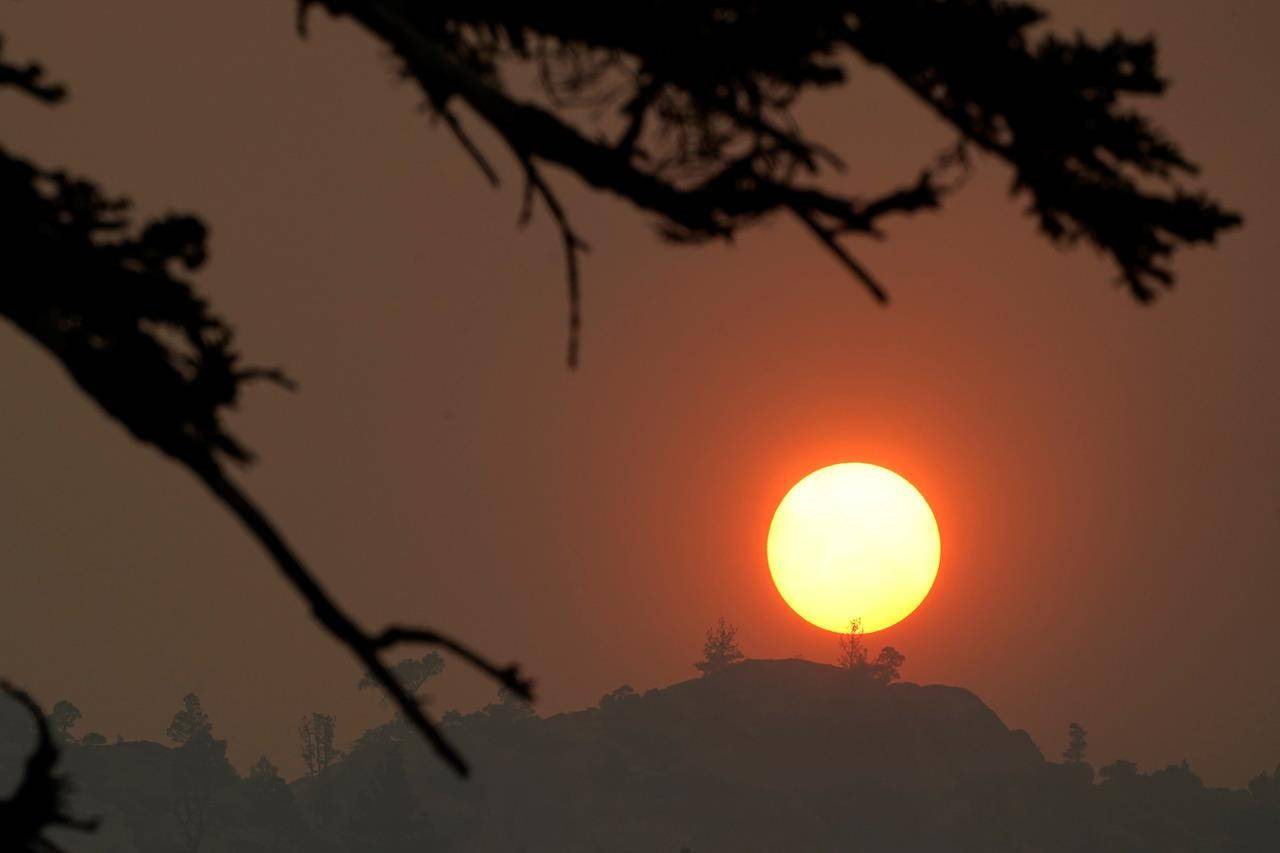 Smoke from the Caldor Fire obscures the sun as it sets over the mountains near South Lake Tahoe, Calif., Tuesday, Aug. 24, 2021. The massive wildfire, that is over a week old, has scorched more than 190 square miles, (492 square kilometers) and destroyed hundreds of homes since Aug. 14. It is now less than 20 miles from Lake Tahoe. (AP Photo/Rich Pedroncelli)