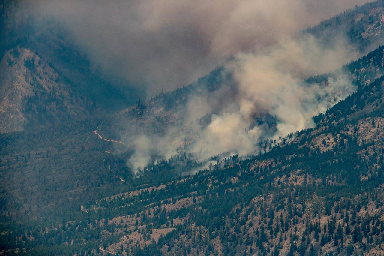 A wildfire burns in the mountains above Lytton, B.C., on Thursday, July 1, 2021. THE CANADIAN PRESS/Darryl Dyck