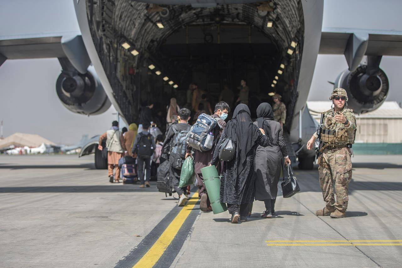 In this image provided by the U.S. Marine Corps, families begin to board a U.S. Air Force Boeing C-17 Globemaster III during an evacuation at Hamid Karzai International Airport in Kabul, Afghanistan, Monday, Aug. 23, 2021. THE CANADIAN PRESS/Sgt. Samuel Ruiz/U.S. Marine Corps via AP