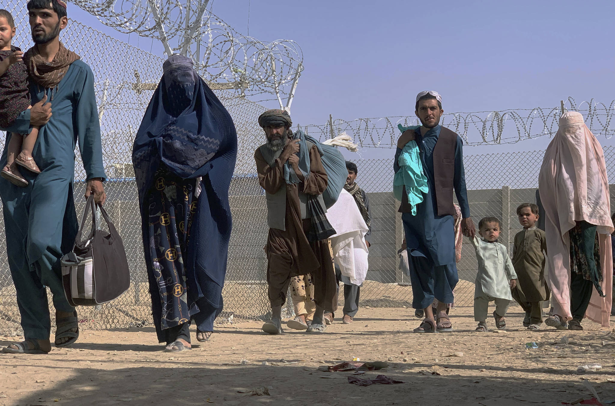 Afghans walk through a security barrier as they enter Pakistan through a common border crossing point in Chaman, Pakistan, Thursday, Aug. 26, 2021. Hundreds of Pakistanis and Afghans cross the border daily through Chaman to visit relatives, receive medical treatment and for business-related activities. Pakistani has not placed any curbs on their movement despite recent evacuations from Kabul. (AP Photo)