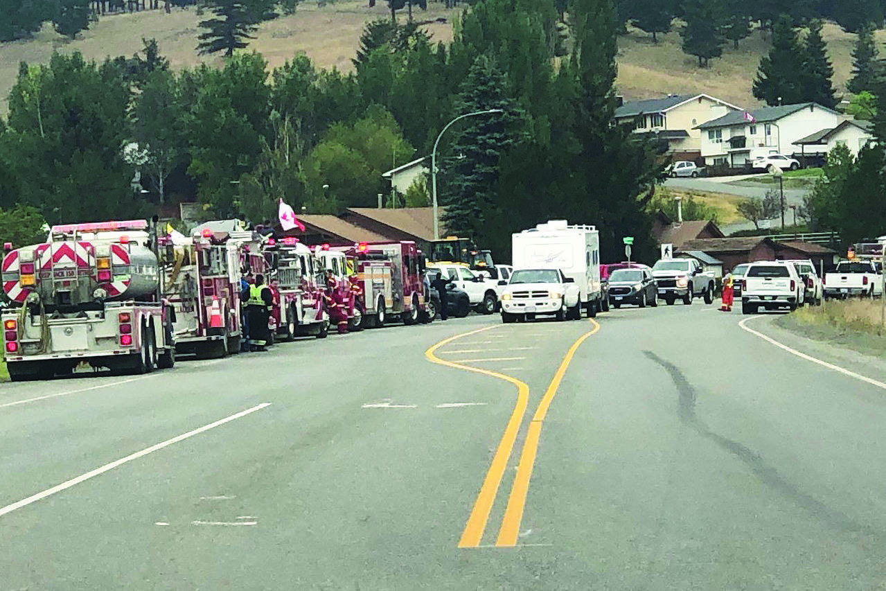 Residents drive past fire crews as they return to Logan Lake on Aug. 19, a week after the community was evacuated because of the Tremont Creek wildfire. (Photo credit: TNRD)