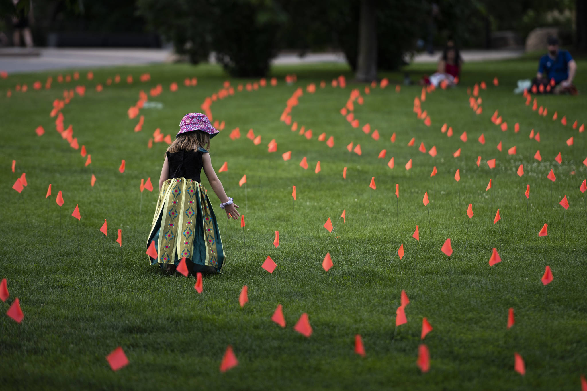 Margot King, 4, touches an orange flag, representing children who died while attending Indian Residential Schools in Canada, placed in the grass at Major's Hill Park in Ottawa, on Canada Day, Thursday, July 1, 2021. THE CANADIAN PRESS/Justin Tang