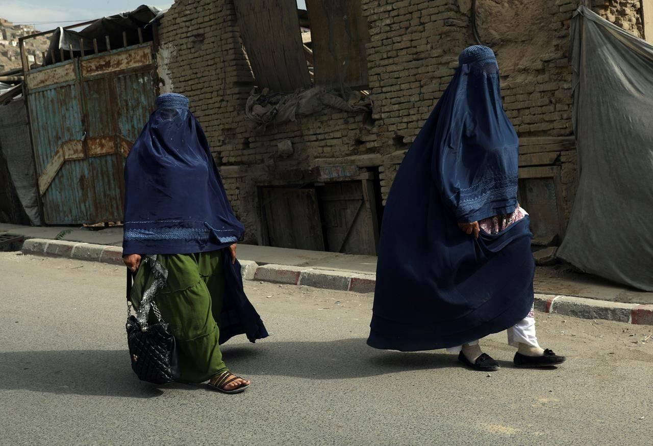 Afghan women in burqas walk on a street in Kabul, Afghanistan, Sunday, Aug. 22, 2021. THE CANADIAN PRESS/AP-Rahmat Gul