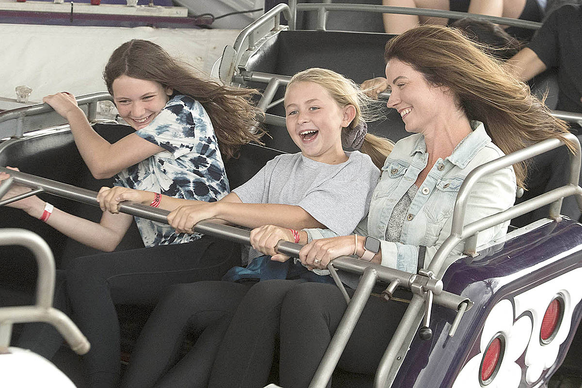 Sophia Sello, 11, Jordyn Hagen, 10, and Laura Sello of Langley were all smiles riding the Music Express at Playland during opening day of the 2021 PNE Fair FUNdamentals. (PNE'S Craig Hodge/Special to Langley Advance Times)