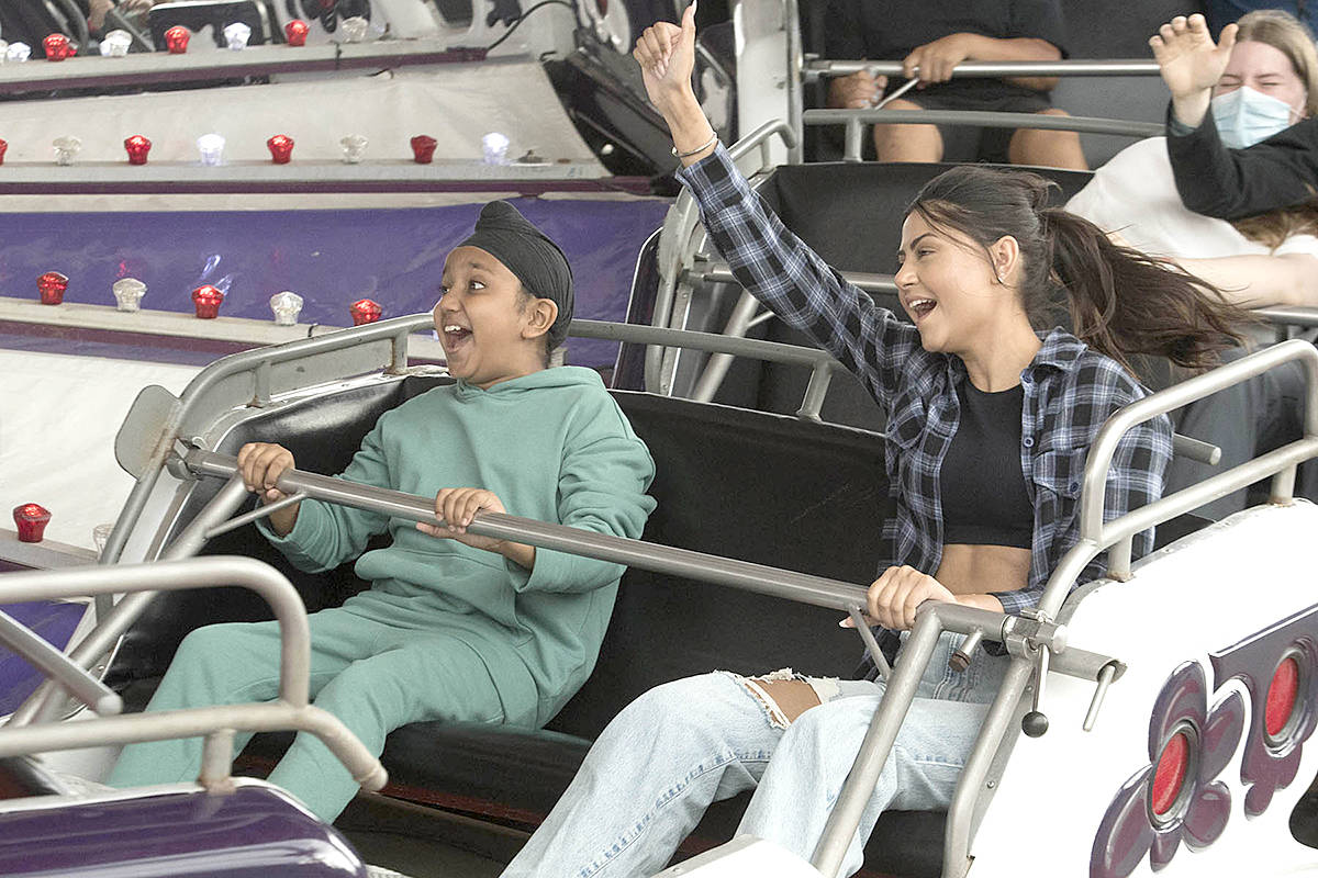 Thumbs up! Akaljeet, nine, and Jasmeet Boparai, 23, of Langley were all smiles riding the Music Express at Playland during opening day of the 2021 PNE Fair FUNdamentals. (PNE'S Craig Hodge/Special to Langley Advance Times)