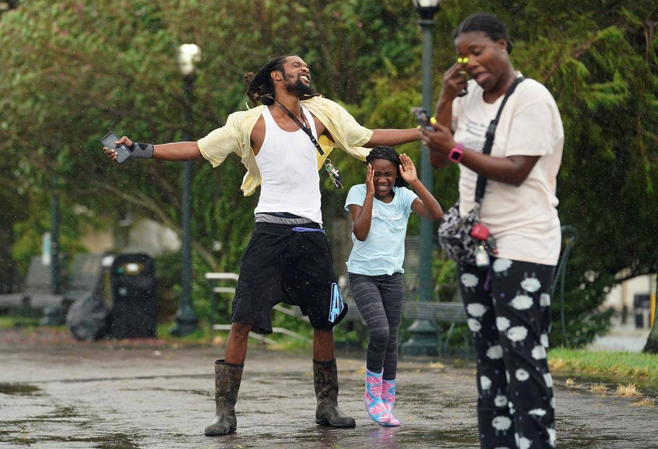 Tony Hilliard, left, and his family expose themselves to the elements as Hurricane Ida begins to make landfall, Sunday, Aug. 29, 2021, in New Orleans, La. (AP Photo/Eric Gay)