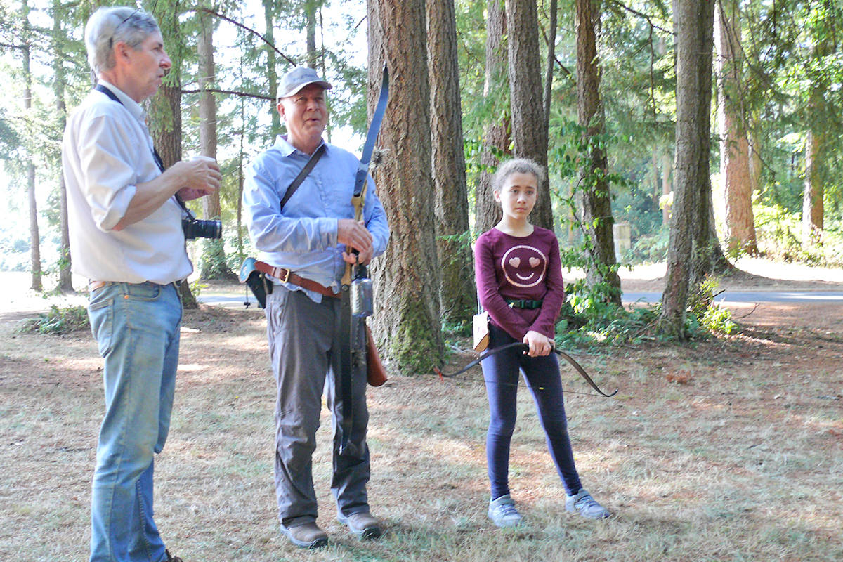 Andy Plumridge (left), chair of the Langley Rod and Gun Cub archery committee, talks with Richard Hall and Hall's granddaughter, Ivy Weents, as they wait to take their turn at a 3D archery event at the club that sent archers into the woods after Styrofoam targets. (Dan Ferguson/Langley Advance Times)