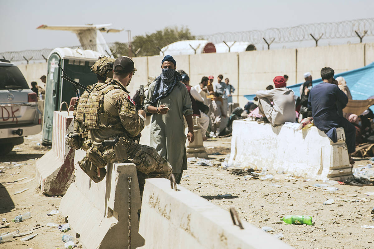 In this photo provided by the U.S. Marine Corps, Canadian coalition forces assist during an evacuation at Hamid Karzai International Airport in Kabul, Afghanistan, Tuesday, Aug. 24, 2021. (Staff Sgt. Victor Mancilla/U.S. Marine Corps via AP)