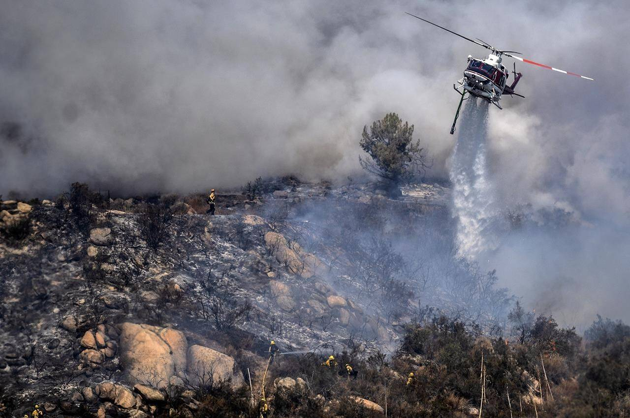 Firefighters are dwarfed by an aerial drop at the the Chaparral Fire in Murrieta, Calif., which still blazes, Sunday, Aug. 29, 2021. Several homes appear to be evacuated in the area. (Cindy Yamanaka/The Orange County Register via AP)