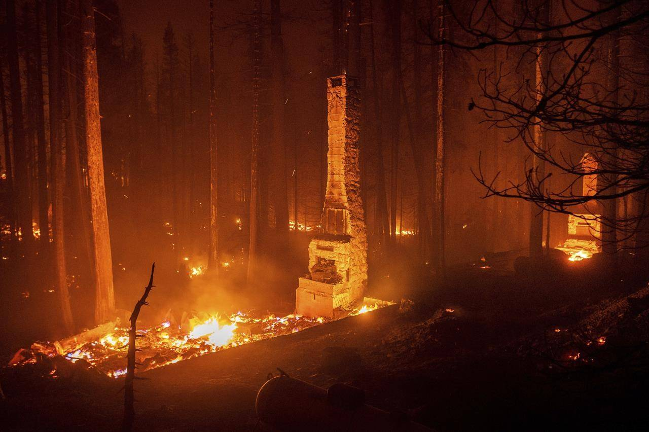 Seen in a long camera exposure, chimneys stand at residences leveled by the Caldor Fire along Highway 50 on Sunday, Aug. 29, 2021, in Eldorado National Forest, Calif. (AP Photo/Noah Berger)