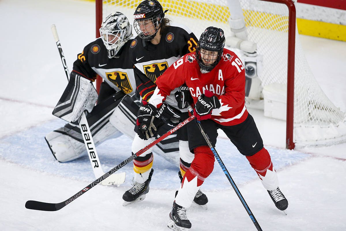Canada's Brianne Jenner, right, and Germany's Tabea Botthof, centre, battle for position as goalie Sandra Abstreiter looks on during third period quarterfinal IIHF Women's World Championship hockey action in Calgary, Saturday, Aug. 28, 2021.THE CANADIAN PRESS/Jeff McIntosh