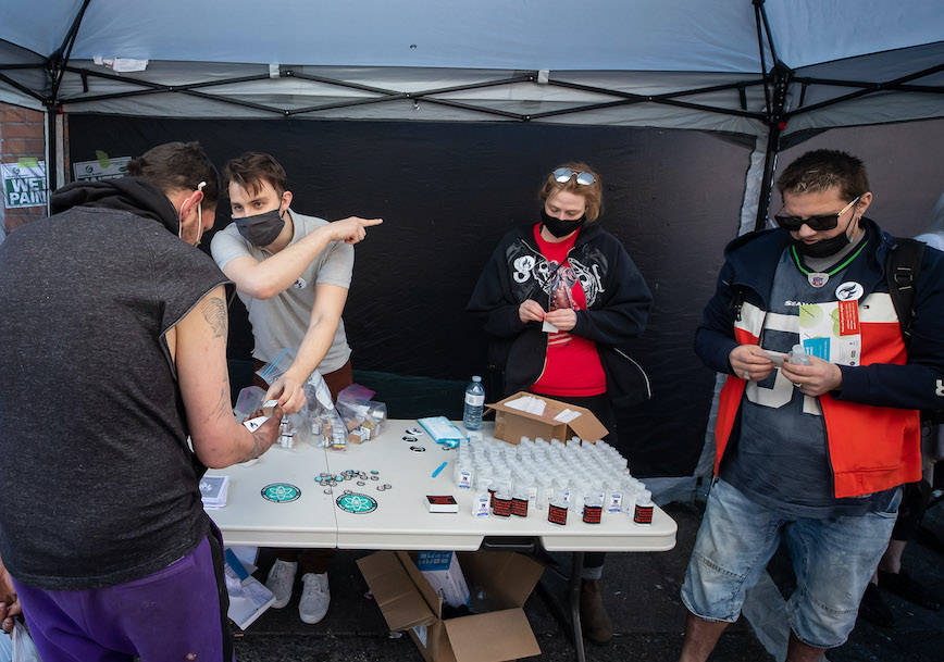 A person receives heroin from the Drug User Liberation Front, who were handing out a safe supply of illicit drugs in the Downtown Eastside to mark the five-year anniversary of British Columbia declaring a public health emergency in the overdose crisis, in Vancouver, on Wednesday, April 14, 2021. THE CANADIAN PRESS/Darryl Dyck