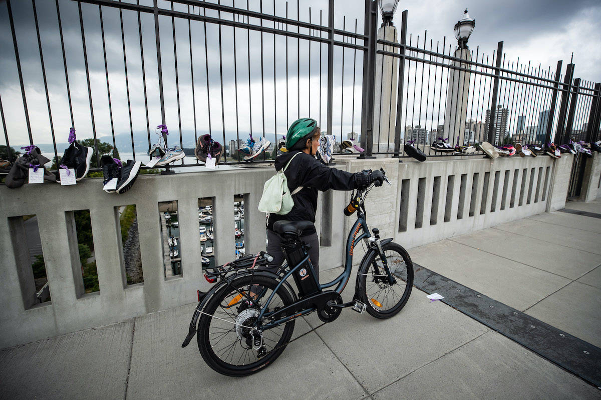 A woman walks a bike past shoes hung on the Burrard Bridge in remembrance of victims of illicit drug overdose deaths on International Overdose Awareness Day, in Vancouver, on Monday, August 31, 2020. THE CANADIAN PRESS/Darryl Dyck