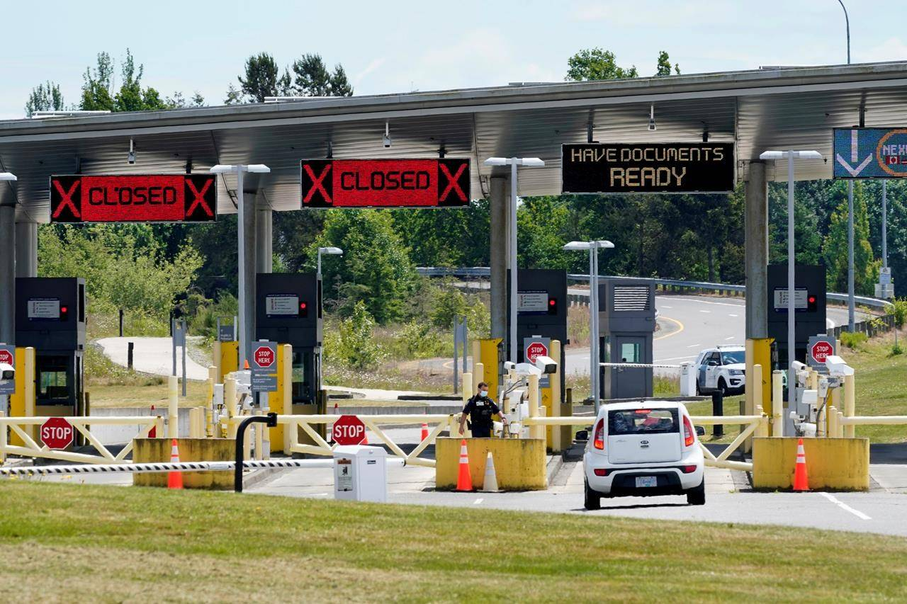 """A car approaches one of the few lanes open at the Peace Arch border crossing between Canada and the United States, in Blaine, Wash., June 8, 2021. The U.S. State Department is now urging Americans to """"reconsider travel"""" to Canada due to what the Centers for Disease Control call """"high"""" levels of COVID-19 infection. THE CANADIAN PRESS/AP-Elaine Thompson"""