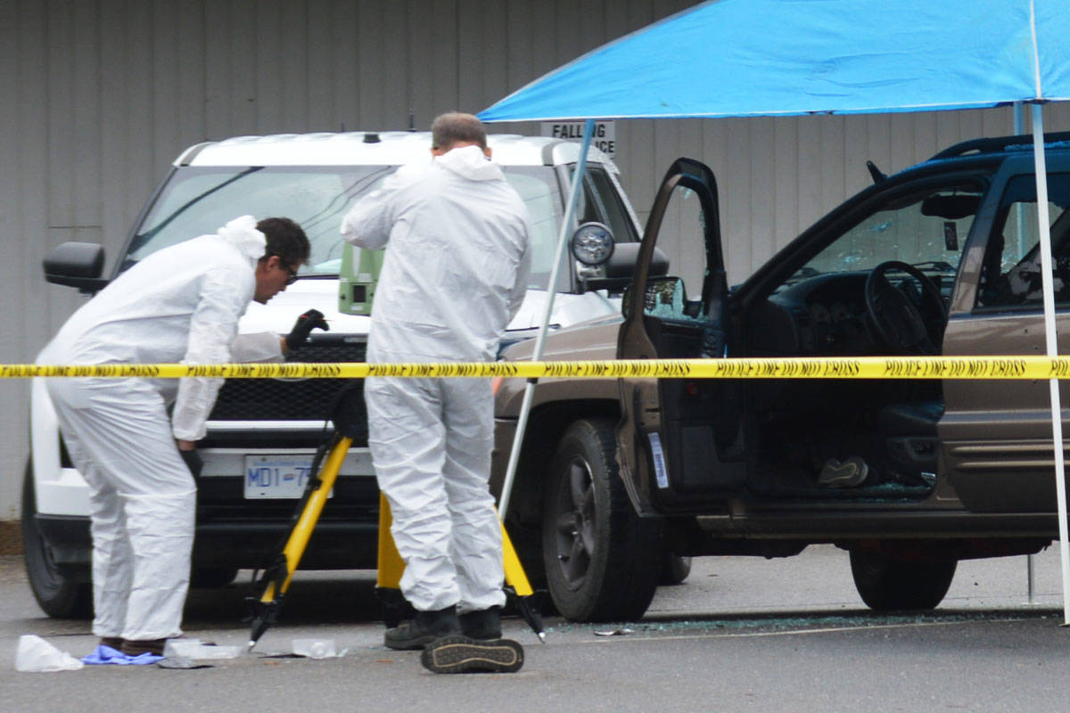 Investigators examine an SUV with what appear to be bullet holes in its windshield and door in the parking lot of the Quesnel Seniors' Centre. (Cassidy Dankochik Photo - Quesnel Cariboo Observer)