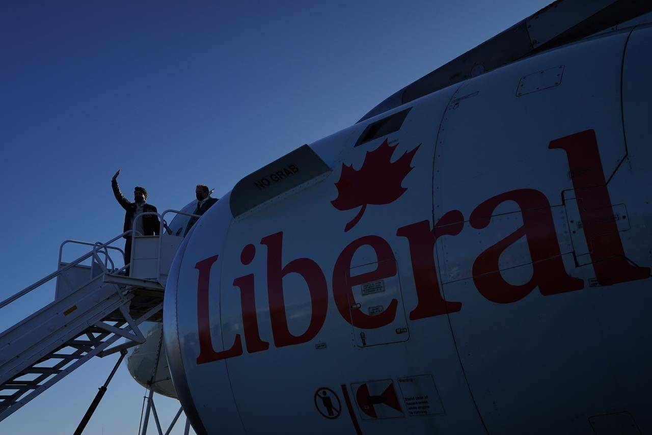 Liberal Leader Justin Trudeau waves from the steps of his campaign plane as he arrives in Iqaluit, Nunavut on Monday, August 30, 2021. THE CANADIAN PRESS/Nathan Denette