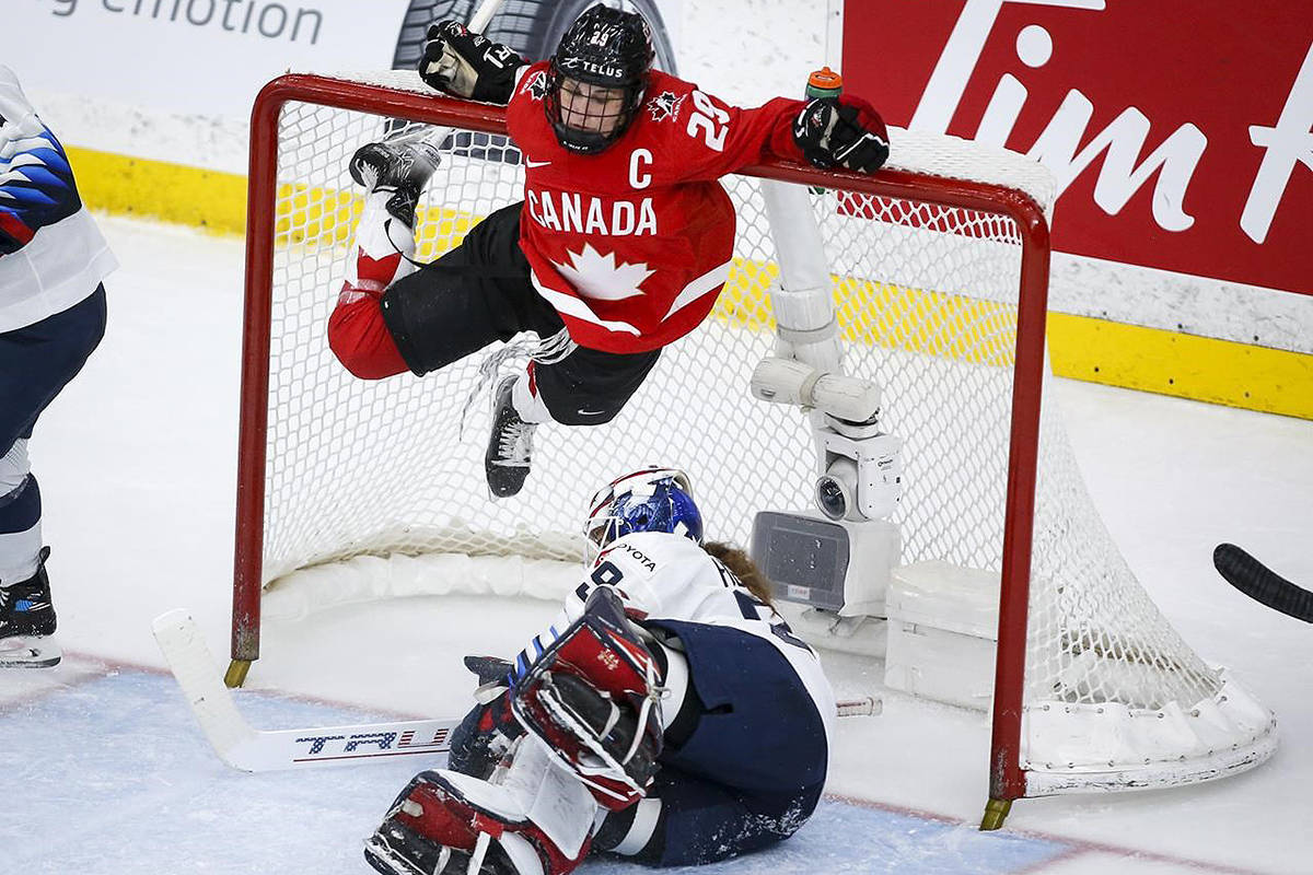 Canada's Marie-Philip Poulin, top, hangs from the cross bar after crashing into goalie Nicole Hensley, of the United States, during third period gold medal final IIHF Women's World Championship hockey action in Calgary, Tuesday, Aug. 31, 2021.THE CANADIAN PRESS/Jeff McIntosh