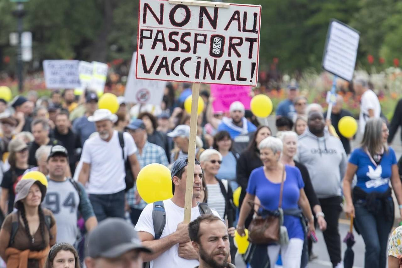 People hold up signs during a demonstration opposing the Quebec government's measures to help curb the spread of COVID-19 in Montreal, Saturday, Aug. 28, 2021. THE CANADIAN PRESS/Graham Hughes