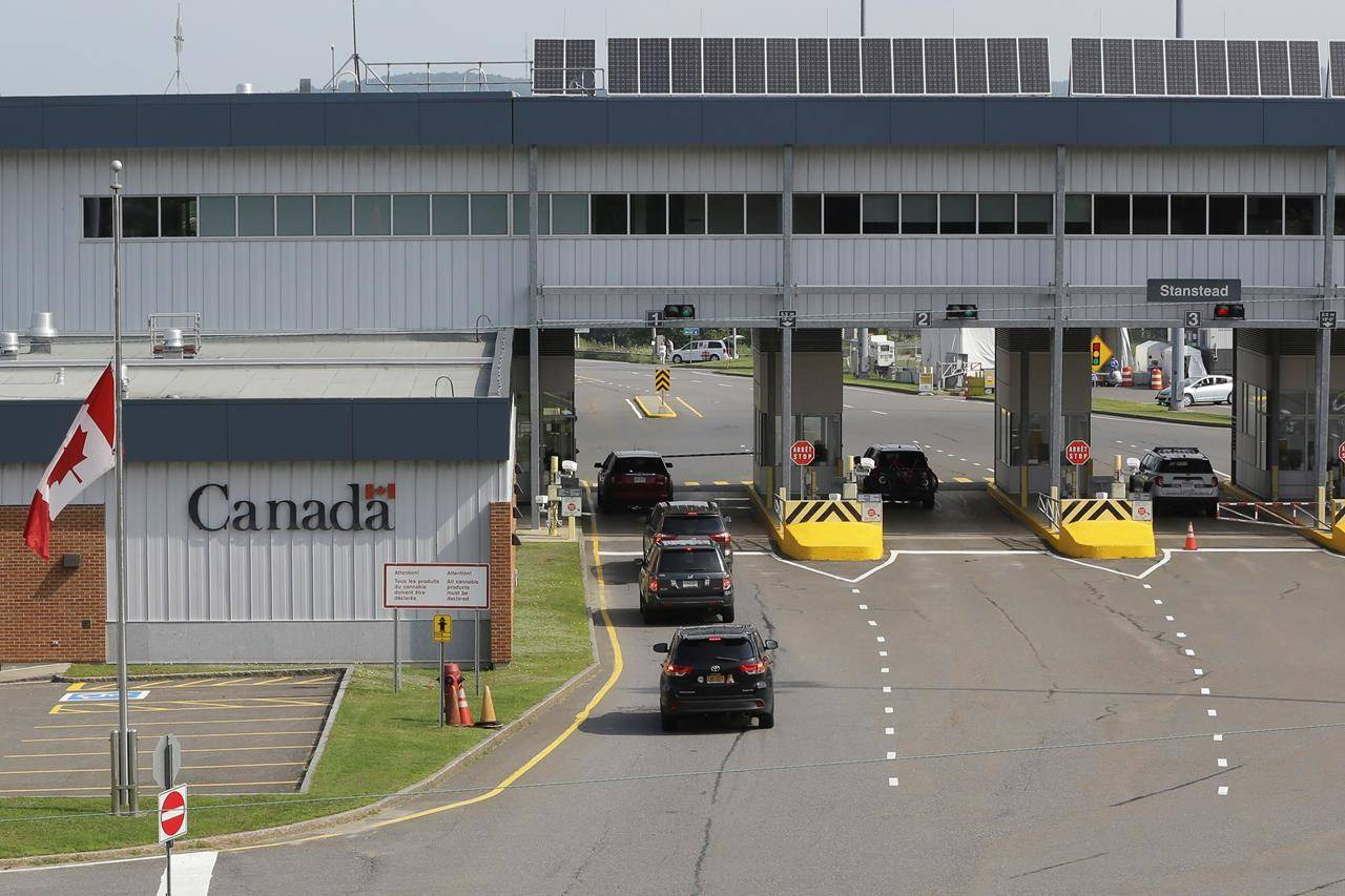 Cars with U.S. licence plates enter Canada at the Stanstead, Quebec, border crossing as seen from Derby Line, Vt., Monday Aug. 9, 2021. THE CANADIAN PRESS/AP-Wilson Ring