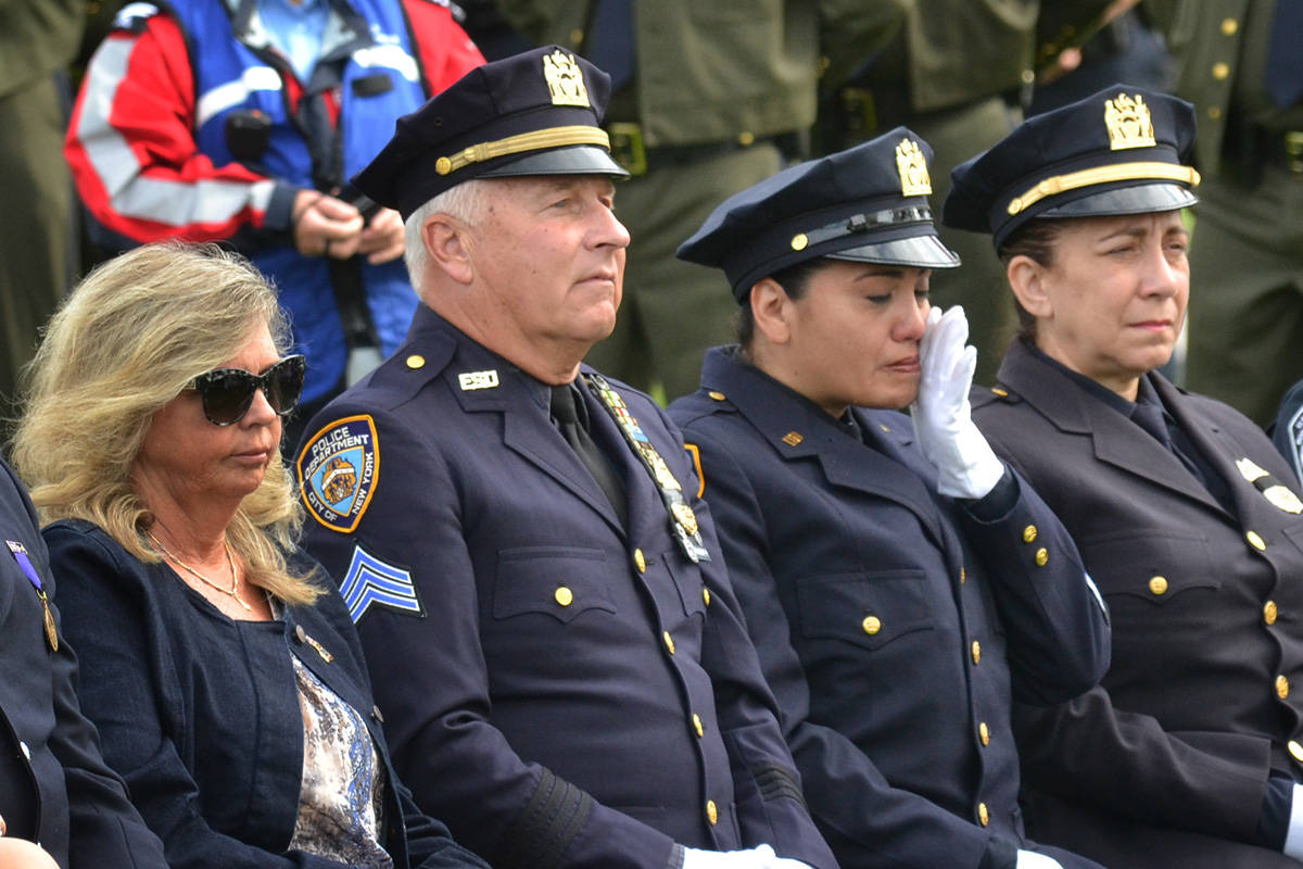 A New York Police Department officer wipes away a tear during a past Sept. 11 memorial ceremony at Peace Arch Park. (File photo)