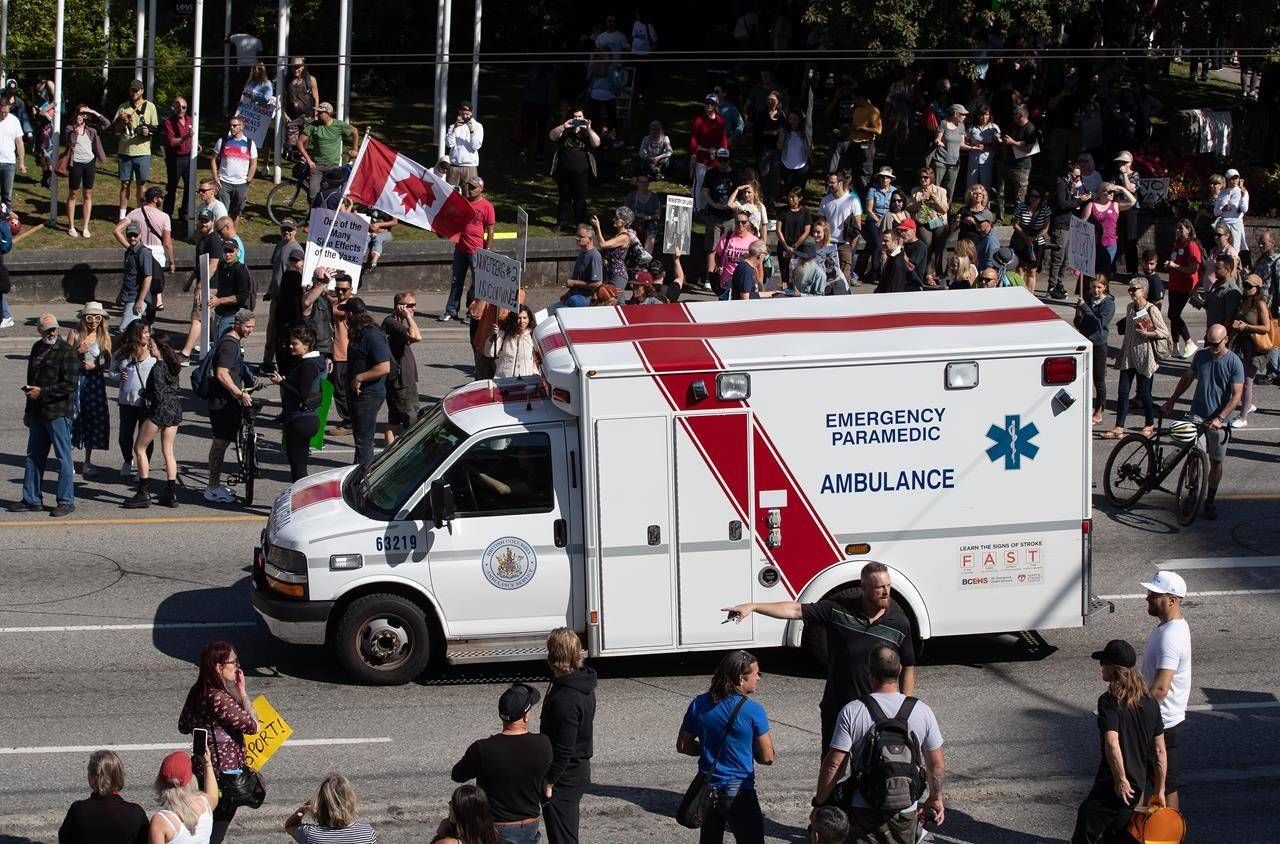 An ambulance passes through a crowd of people protesting COVID-19 vaccine passports and mandatory vaccinations for health-care workers, in Vancouver, on Wednesday, Sept. 1, 2021. The protest began outside Vancouver General Hospital and police estimated the crowd gathered to be as many as 5,000 people. THE CANADIAN PRESS/Darryl Dyck