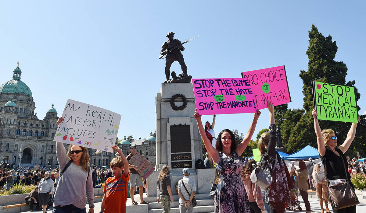Protesters raise homemade signs in front of the B.C. Legislature calling for the B.C. vaccine card to be scrapped. (Don Denton/VicNews)