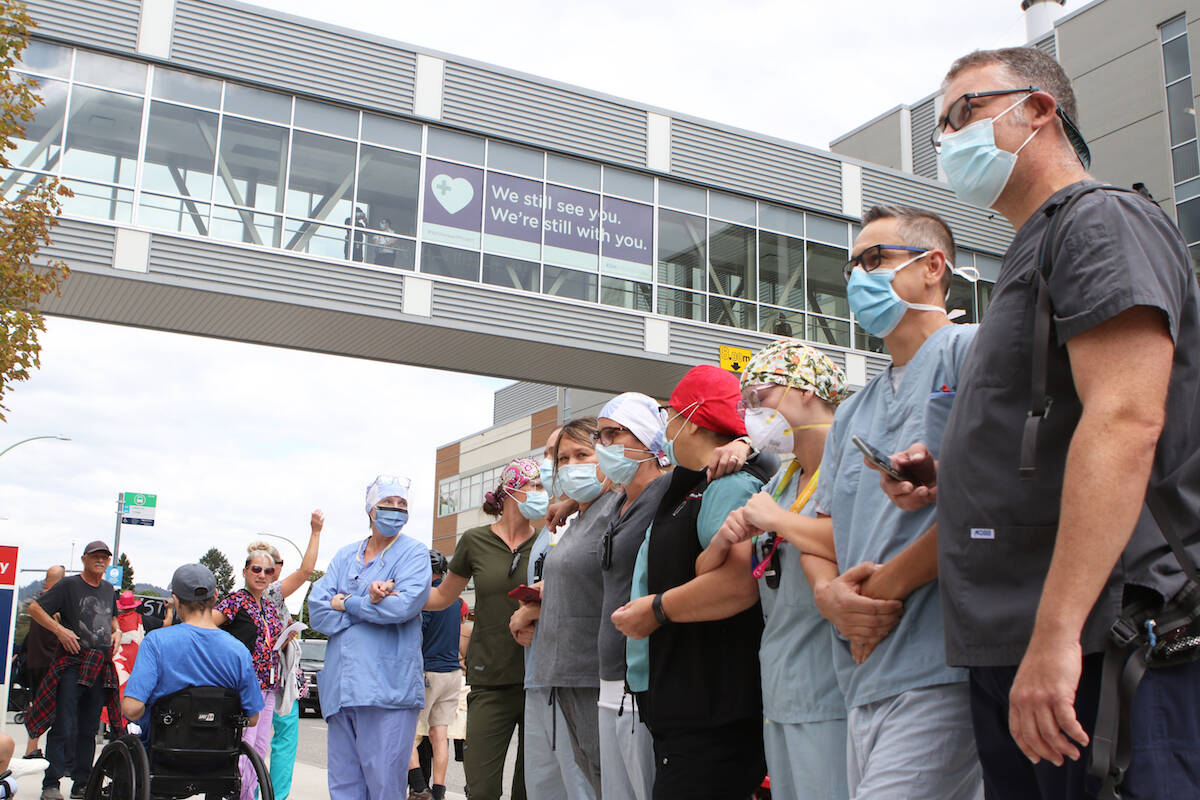 Kelowna General Hospital nurses stand outside the hospital with locked arms, opposing a group of roughly 1,000 people who protested COVID-19 health measures outside of the hospital on Sept. 1. (Aaron Hemens/Capital News)