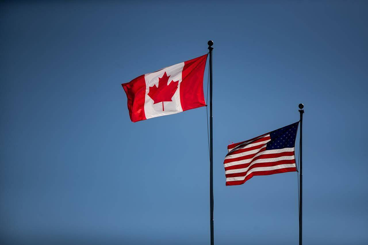 Canada and U.S. flags fly in the wind at the Douglas-Peace Arch border crossing, in Surrey, B.C., on Monday, March 16, 2020. The Canadian Chamber of Commerce wants federal leaders to get serious about making critical minerals a fundamental part of North America's economic recovery. THE CANADIAN PRESS/Darryl Dyck