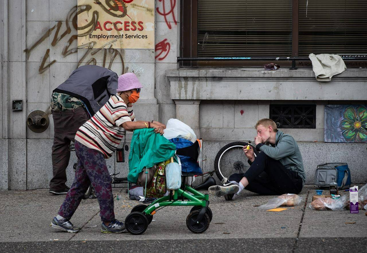 A woman walks past a person using a glass pipe to smoke drugs in the Downtown Eastside of Vancouver, on International Overdose Awareness Day on Tuesday, August 31, 2021. THE CANADIAN PRESS/Darryl Dyck