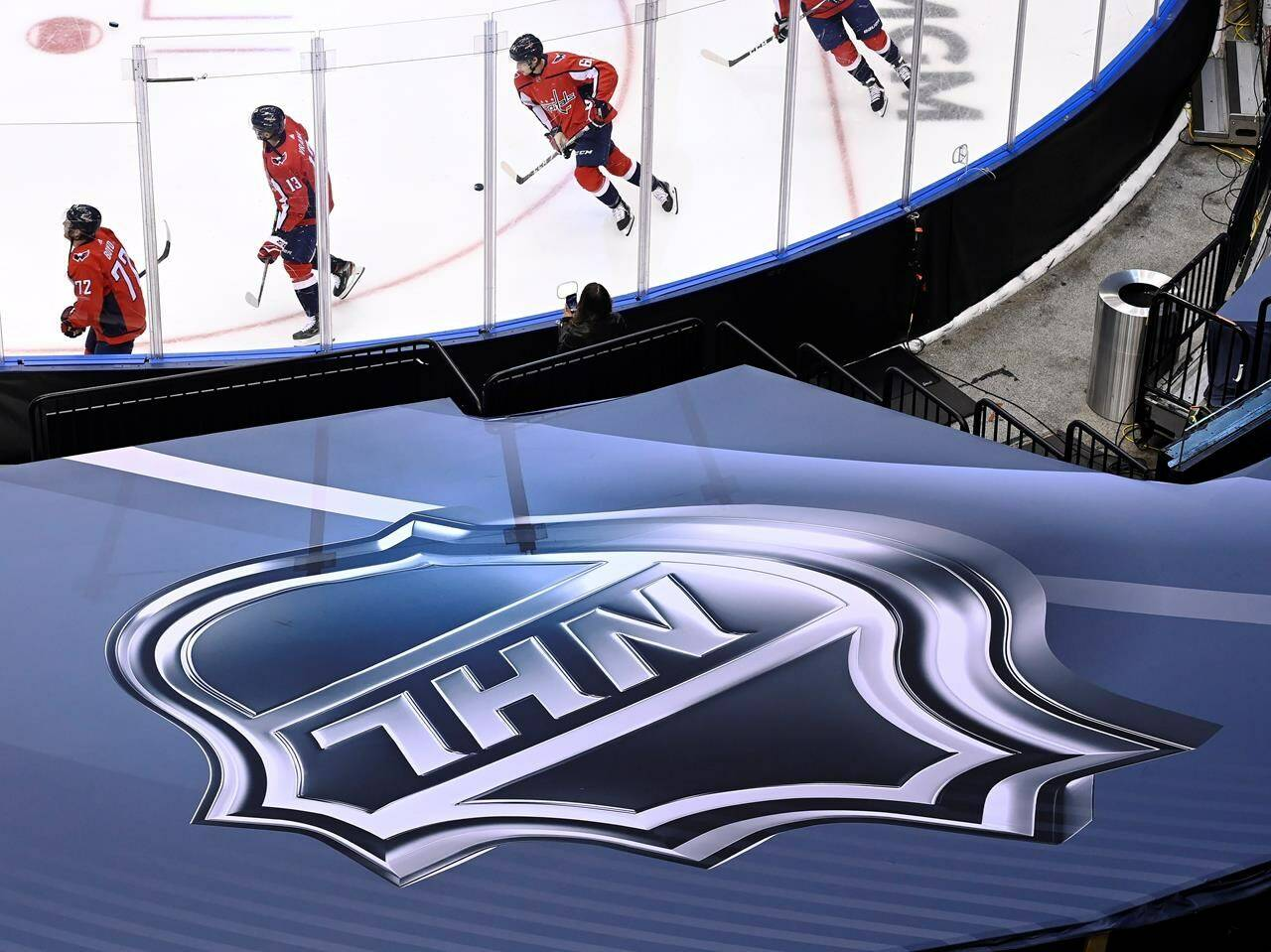 In this Aug. 14, 2020, file photo, an NHL logo is displayed as Washington Capitals players skate prior to NHL Eastern Conference Stanley Cup playoff hockey game against the New York Islanders in Toronto. (Nathan Denette/The Canadian Press via AP)