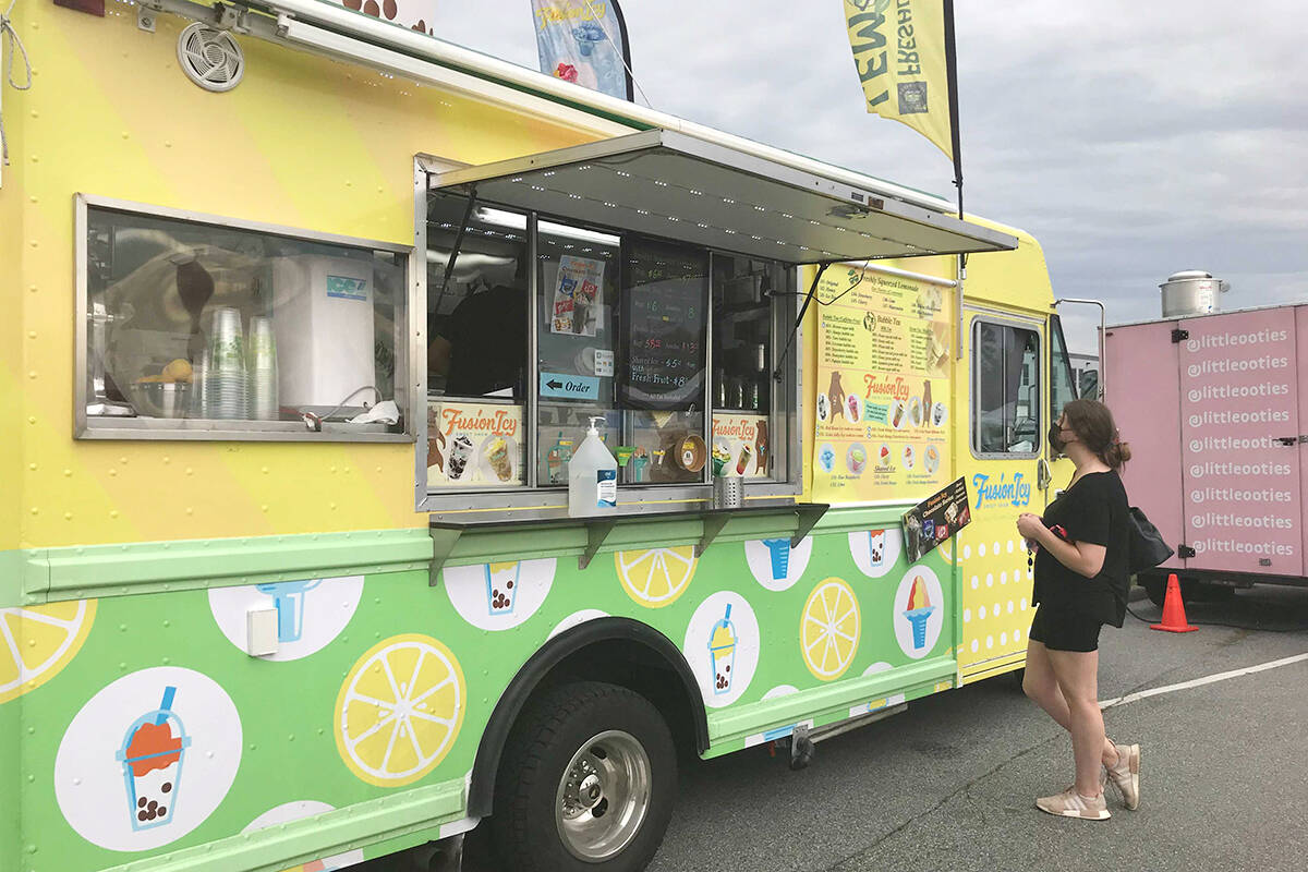 One of the vendors at the Langley Food Truck Festival serves a customer on Friday, Sept. 3. (Matthew Claxton/Langley Advance Times)