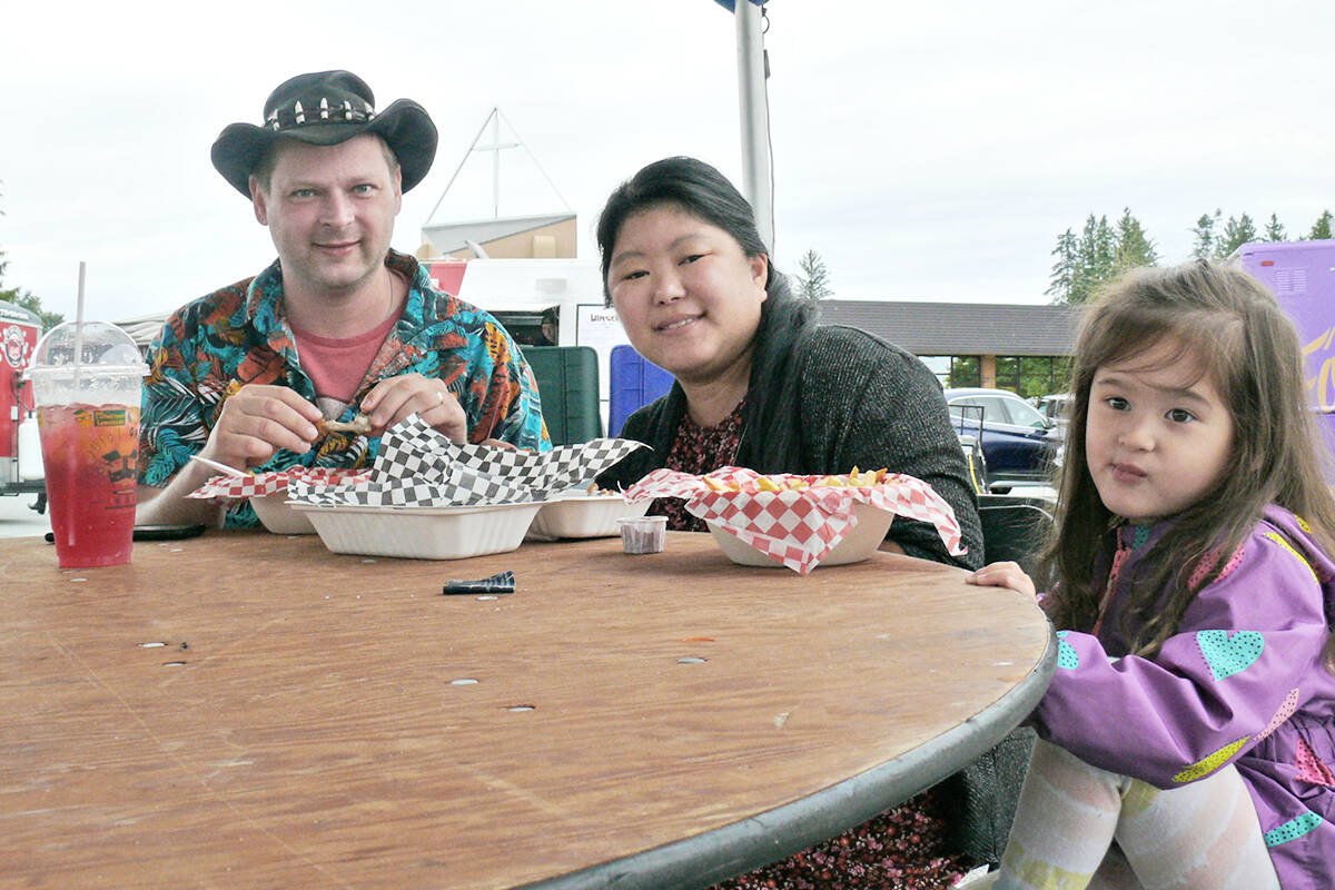 Wayne and Joy Toews and daughter Trinity, from Willoughby, tucked into lunch at the Langley Food Truck Festival on Saturday, Sept. 4. (Dan Ferguson/Langley Advance Times)