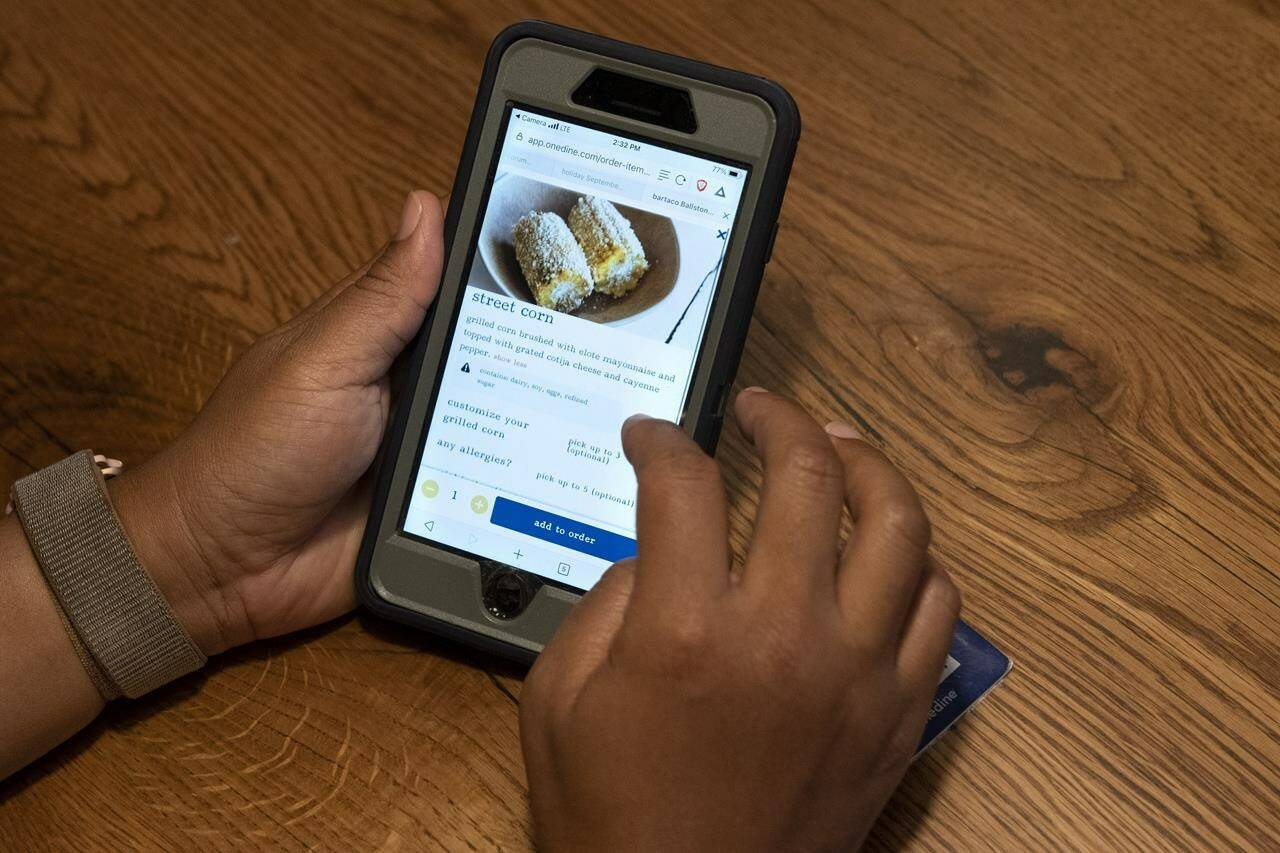 """A diner at Bartaco uses their app to order an item off the menu, at the restaurant in Arlington, Va., on Thursday, Sept. 2, 2021. The restaurant is using an automated app for ordering and payments. Instead of servers they use """"food runners"""" to get the food to the tables. (AP Photo/Jacquelyn Martin)"""
