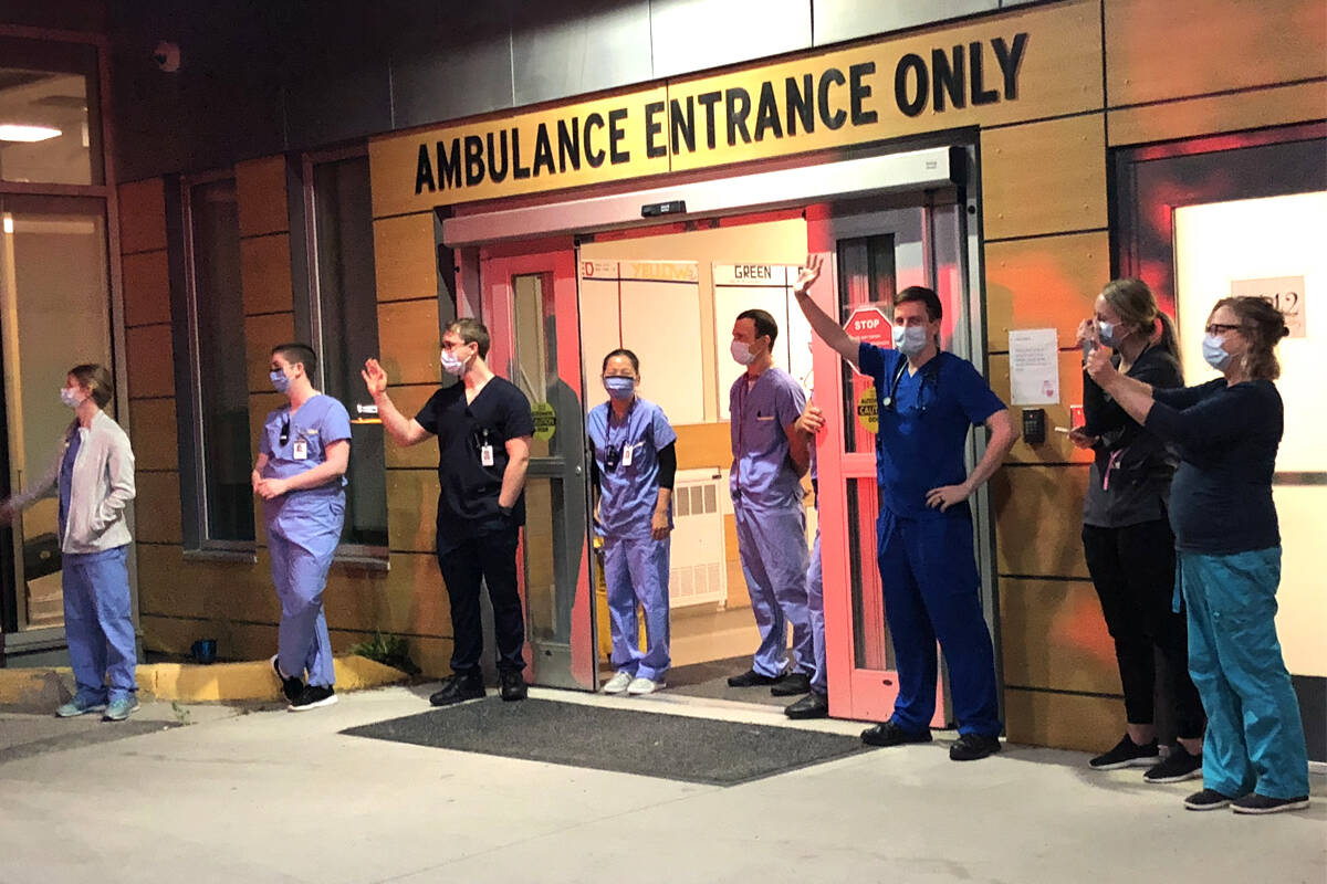 Doctors and nurses gathered outside the emergency room at Nelson's Kootenay Lake Hospital on Friday evening as local police and firefighters paraded by to show support. Photo: Tyler Harper