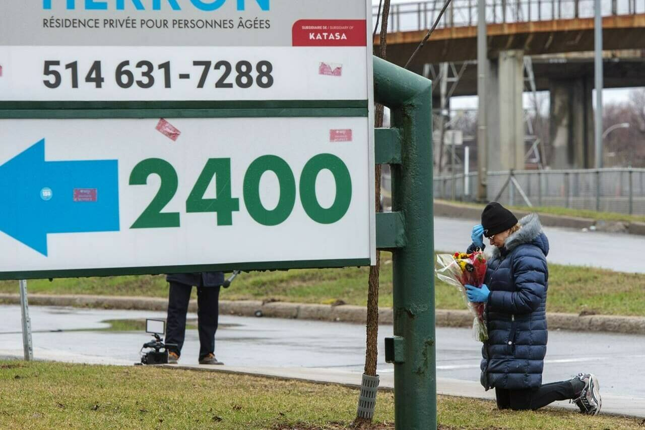 A woman prays in front of the Herron seniors residence Monday April 13, 2020 in Dorval near Montreal's Trudeau airport. THE CANADIAN PRESS/Ryan Remiorz