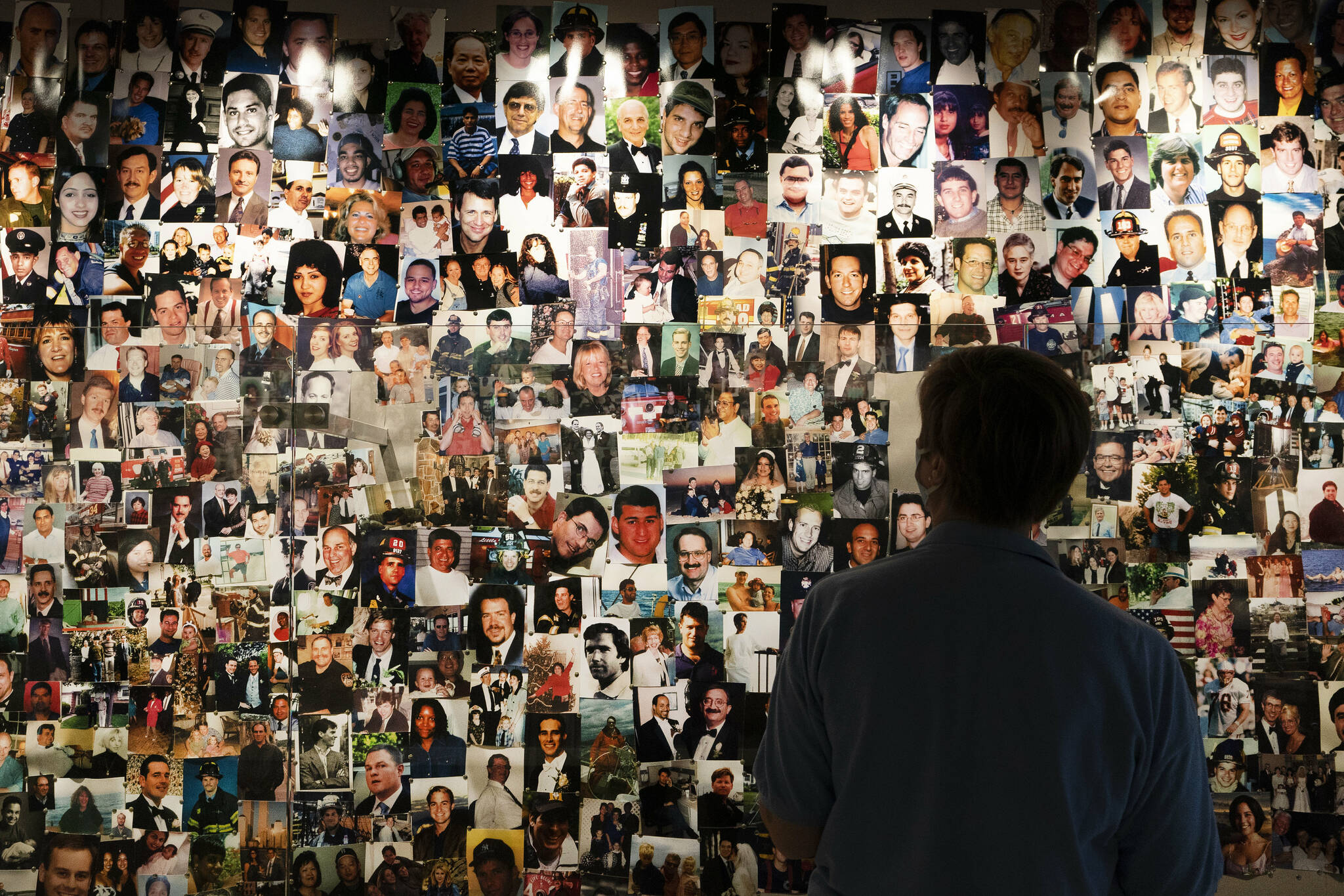 Désirée Bouchat, a survivor of the 9/11 attacks on the World Trade Center, looks at photos of those who perished, in a display at the 9/11 Tribute Museum, Friday, Aug. 6, 2021, in New York. While Sept. 11 was a day of carnage, it also was a story of survival: Nearly 3,000 people were killed, but an estimated 33,000 or more people evacuated the World Trade Center and Pentagon. (AP Photo/Mark Lennihan)
