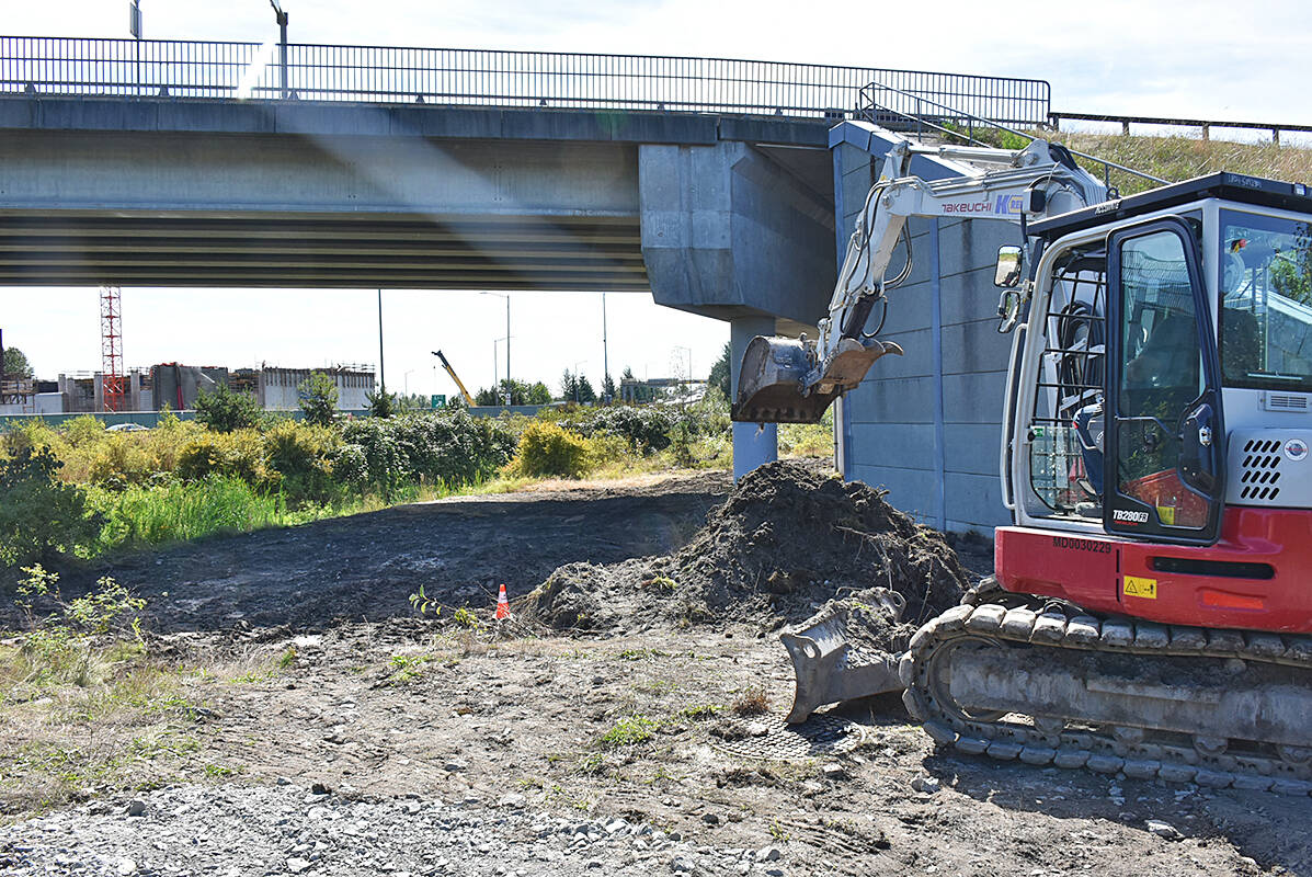 A backhoe works on the site where sewage spilled into Katzie Slough on Friday. (Neil Corbett/The News)
