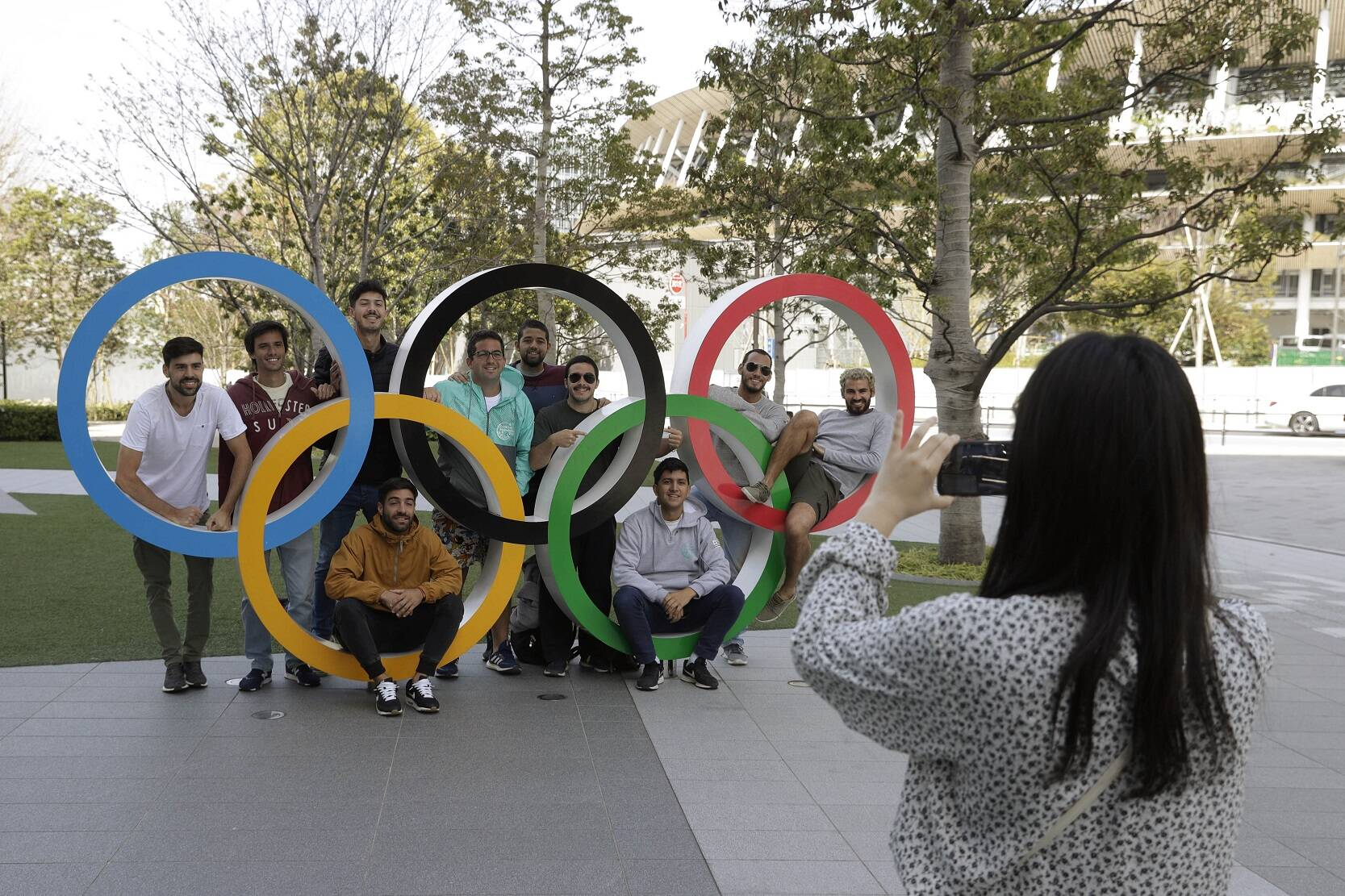 A group of students from Uruguay pose for a souvenir picture on the Olympic Rings set outside the Olympic Stadium in Tokyo, Saturday, March 21, 2020. (AP Photo/Gregorio Borgia)