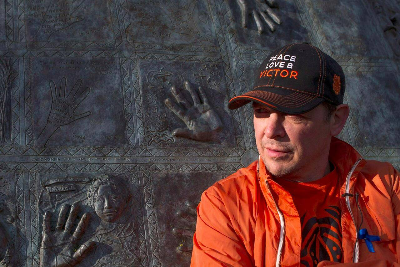 """Former NHLer Theo Fleury stands in front of a child abuse monument as he begins """"The Victor Walk"""" in Toronto on Tuesday, May 14, 2013. Brandon University has issued a statement publicly criticizing Fleury for spreading harmful conspiracy theories.THE CANADIAN PRESS/Chris Young"""