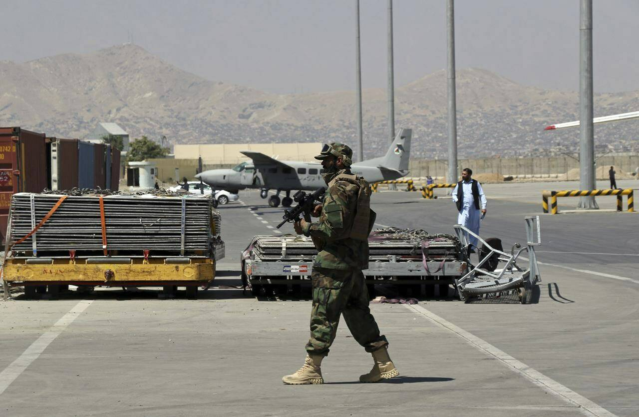 A Taliban soldier walks on the tarmac at Hamid Karzai International Airport in Kabul, Afghanistan, Sunday, Sept. 5, 2021. Some domestic flights have resumed at Kabul's airport, with the state-run Ariana Afghan Airline operating flights to three provinces. (AP Photo/Wali Sabawoon)