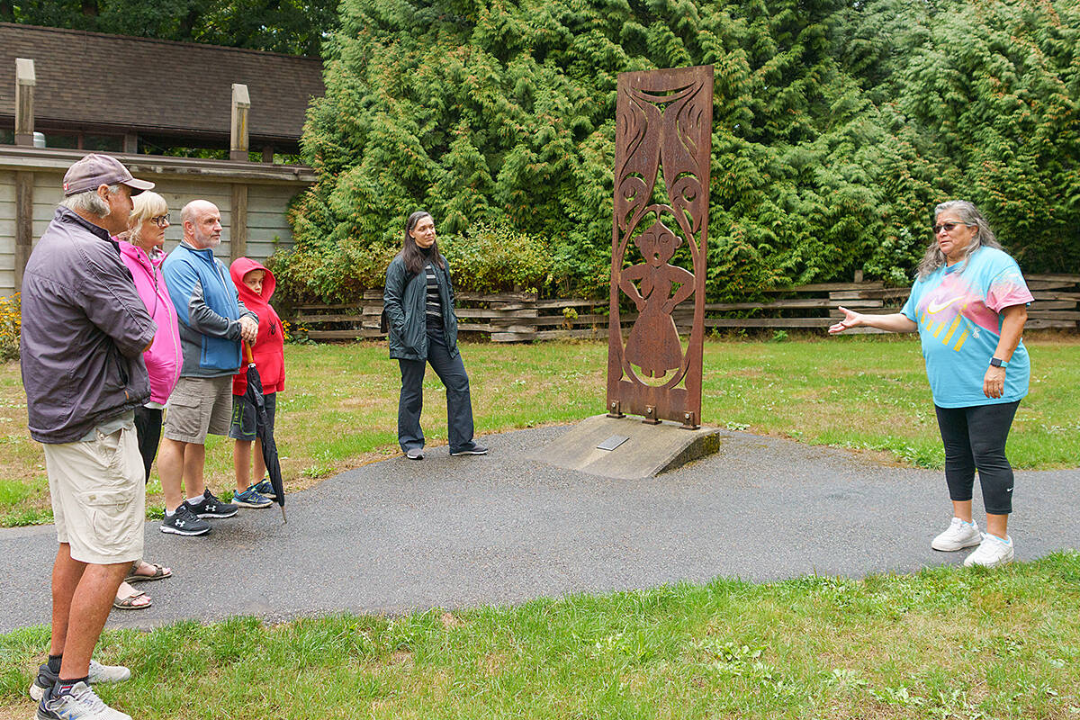 A tour of the Fort Langley National Historic Site included an explanation of this carving that depicts – as it's told – the Kwantlen and Katzie women who helped the fort with the salmon trade. Lou Fasullo shared the picture, interested to learn from Fern Gabriel (right) that the carving depicts the women waiting for the salmon, so they could be salted and brined for their journey to the Sandwich Islands (the name given to the Hawaiian Islands by James Cook in 1778). (Special to Langley Advance Times)