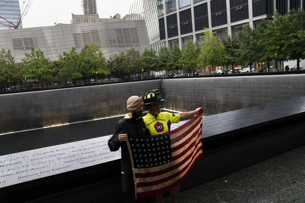 """Retired Santa Clara firefighter Darrell Sales, right, and fellow cyclist Jeremy Provancher, left, stand beside the south pool holding an American flag after completing their """"Bay to Brooklyn"""" bicycle ride at the National September 11 Memorial & Museum, Thursday, Sept. 9, 2021, in New York. A team of current and former firefighters spent 40 days traveling by bicycle to New York City in solidarity for the 20th anniversary of the September 11 terrorist attacks. (AP Photo/John Minchillo)"""