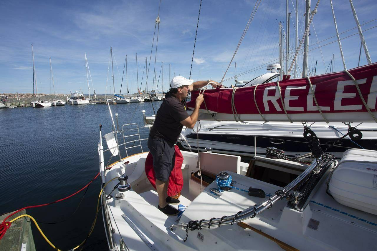 Ken Ryan secures the boom on his sailboat at the Royal Newfoundland Yacht Club before the arrival of Hurricane Larry, in Conception Bay South, N.L., Friday, Sept. 10, 2021. THE CANADIAN PRESS/Paul Daly