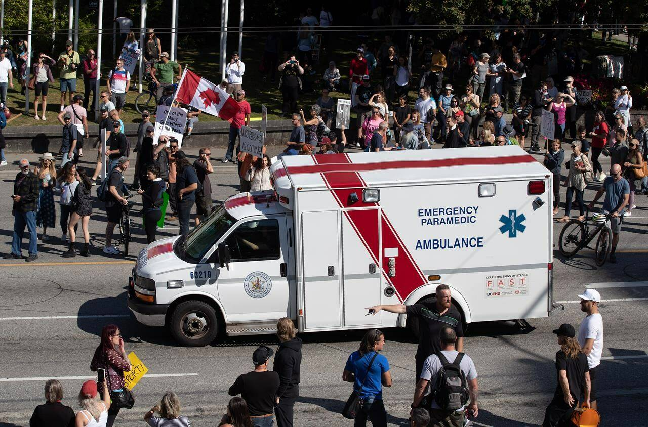 An ambulance passes through a crowd of people protesting COVID-19 vaccine passports and mandatory vaccinations for healthcare workers, in Vancouver, B.C., Wednesday, Sept. 1, 2021. THE CANADIAN PRESS/Darryl Dyck