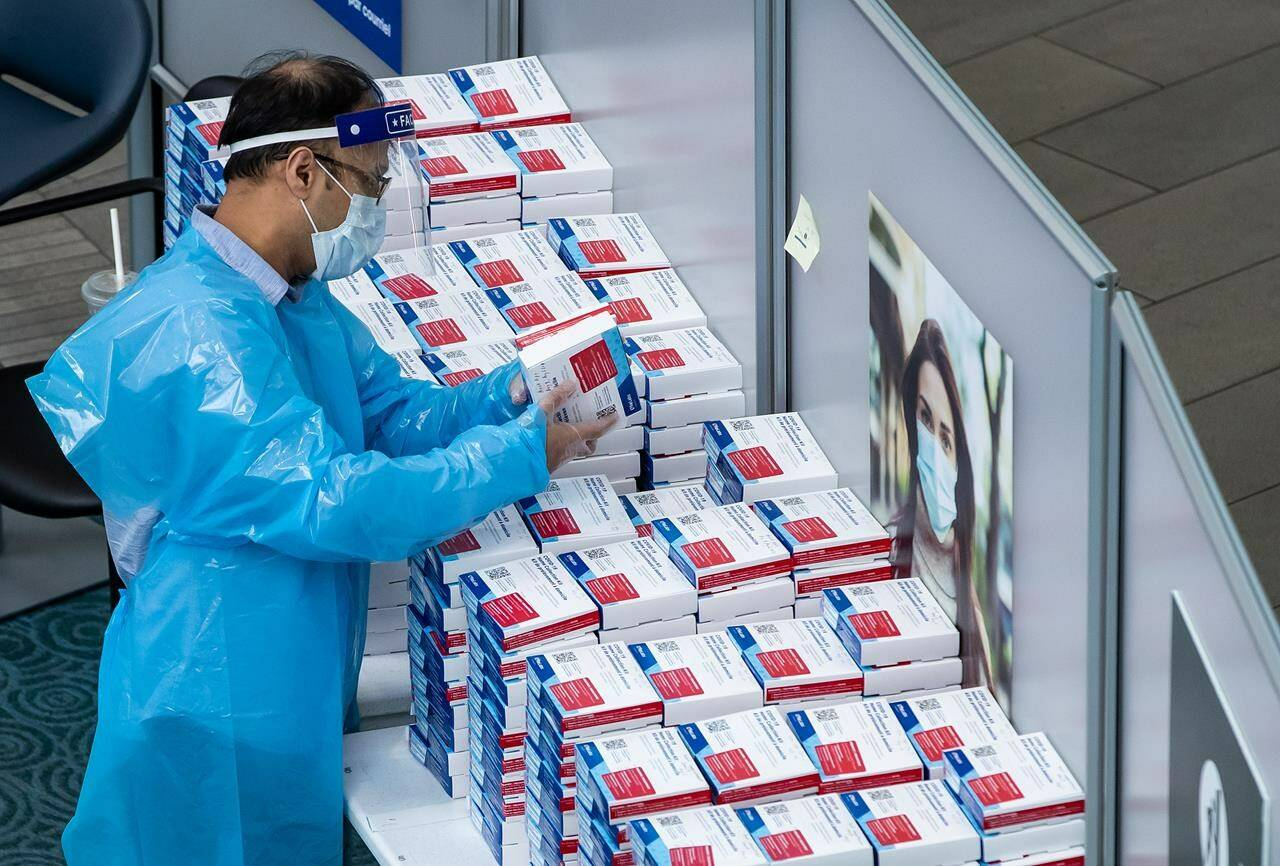 FILE – A worker picks up a COVID-19 self collection test kit which are given to arriving international passengers at Vancouver International Airport, in Richmond, B.C., on Friday, July 30, 2021. THE CANADIAN PRESS/Darryl Dyck