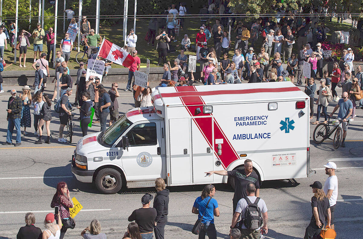An ambulance passes through a crowd of people protesting COVID-19 vaccine passports and mandatory vaccinations for healthcare workers, in Vancouver, on Wednesday, September 1, 2021. The protest began outside Vancouver General Hospital and police estimated the crowd gathered to be as many as 5,000 people. (CANADIAN PRESS/Darryl Dyck)